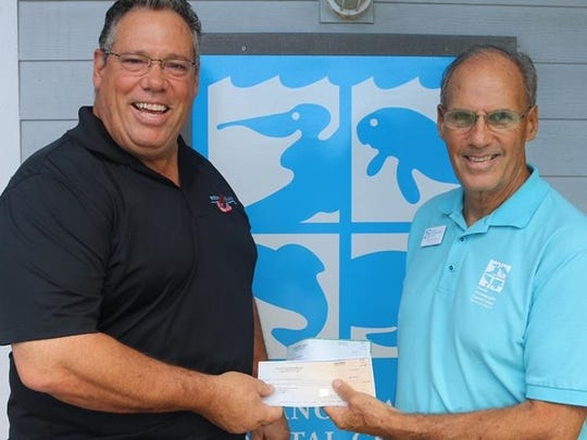 Bob Thesz,restaurant manager at New England Fish Market & Restaurant, presents checks to Mark Perry, executive director of the Florida Oceanographic Society.