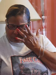 Denise Handy Moss wipes away tears as she reflects