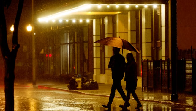 A couple crosses Union Avenue late Friday during a thunderstorm in Knoxville, Tennessee on Friday, April 21, 2017.