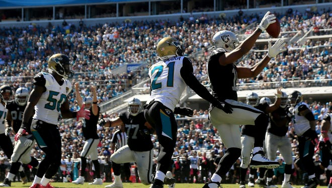 Michael Crabtree of the Oakland Raiders scores a touchdown in front of  Prince Amukamara #21 of the Jacksonville Jaguars during the game at EverBank Field on October 23, 2016 in Jacksonville, Florida.