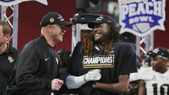 ATLANTA, GA - JANUARY 01:  Head coach Scott Frost of the UCF Knights celebrates with Shaquem Griffin #18 after defeating the Auburn Tigers 34-27 to win the Chick-fil-A Peach Bowl at Mercedes-Benz Stadium on January 1, 2018 in Atlanta, Georgia.  (Photo by Streeter Lecka/Getty Images) ORG XMIT: 775057754 ORIG FILE ID: 900355420