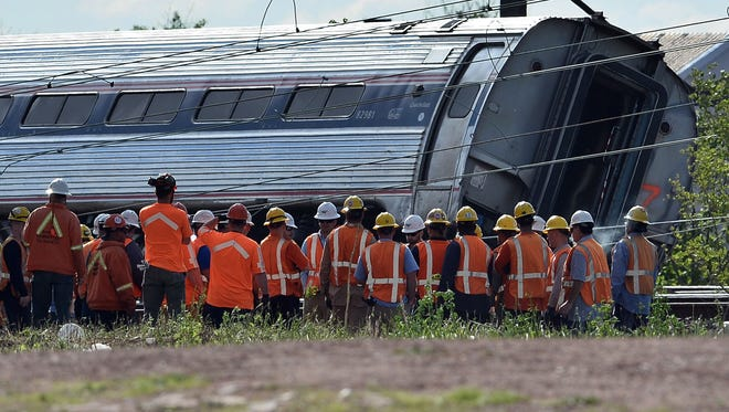Rescue workers gather around a derailed passenger car in Philadelphia on May 13, 2015.