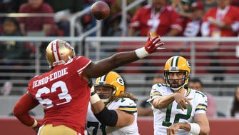 Green Bay Packers quarterback Aaron Rodgers passes the football behind guard Josh Sitton against San Francisco 49ers defensive end Tony Jerod-Eddie during the first quarter at Levi's Stadium.