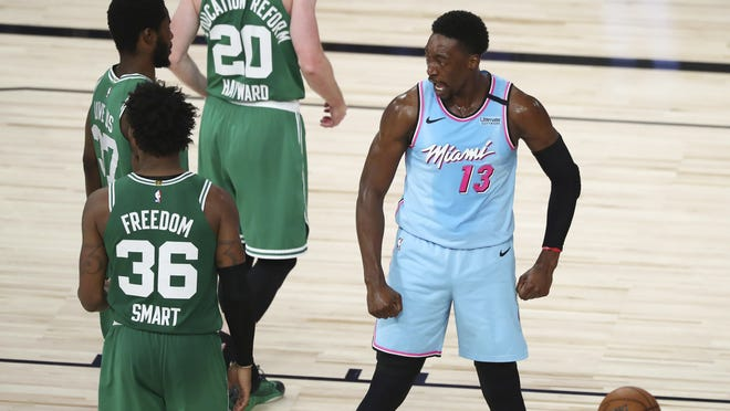 Miami Heat forward Bam Adebayo (right) reacts after scoring and getting fouled against the Boston Celtics during the second half of an NBA basketball game Tuesday in Lake Buena Vista, Fla.