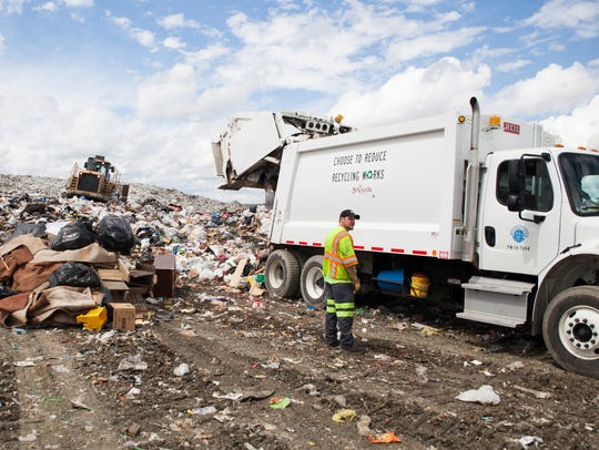 A City of Staunton garbage collector stands by as a