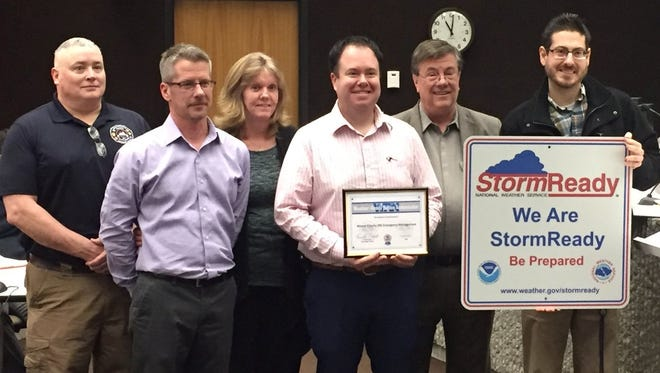 Wayne County's Emergency Management Agency recently received StormReady certification from the National Weather Service. Jon Duke (second from left), Tammy Spears and Matthew Cain (with certificate) received the award during a Wayne County Commissioners meeting.
