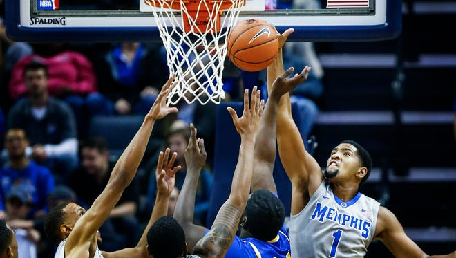 University of Memphis forward Dedric Lawson (right) blocks the shot of McNeese forward Howard Thomas (second right) during frist half action at the FedExForum.