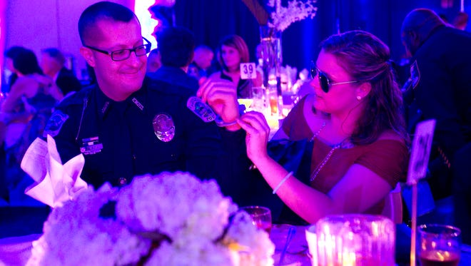 Fort Myers Police Officer Robert Vega is handcuffed by fiance Tiffany LeClerc Friday, October 10 at the Law and Order Ball in Fort Myers.
