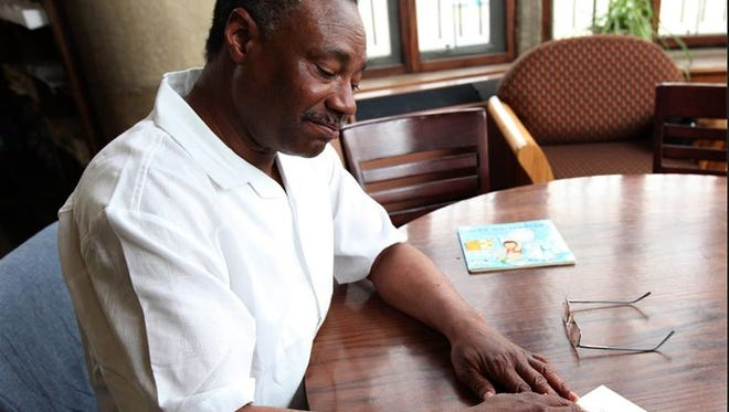 James Samuel, 55, of Highland Park looks at the love letter he wrote to his wife.
