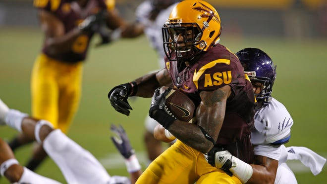 ASU receiver Jaelen Strong is tackled by Weber State linebacker Emmett Tela during the first quarter of a game at Sun Devil Stadium in Tempe on Aug. 28, 2014.