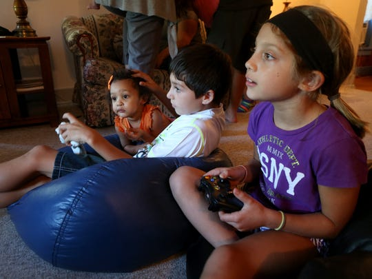 Riley Sundine sits with his little cousin, Hadassah Nerestant, while playing video games with another cousin, Eva Lynn Anderson.