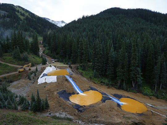 FILE - In this Aug. 12, 2015 file photo, water flows through a series of retention ponds built to contain and filter out heavy metals and chemicals from the Gold King mine chemical accident, in the spillway about 1/4 mile downstream from the mine, outside Silverton, Colo.