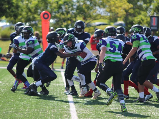 Hobe Sound Ravens running back Logan Lasher, with the assistance of the 13U offense, tries to gain yardage against the Fort Lauderdale Bulls.