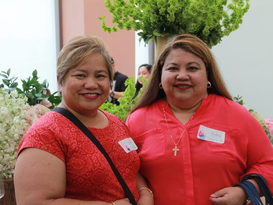 Linda Steiner, left, and Doris Dela Cruz, right, pose in front of a flower display at the Weddings in Paradise show Saturday, March 18 at the Dusit Thani Guam.