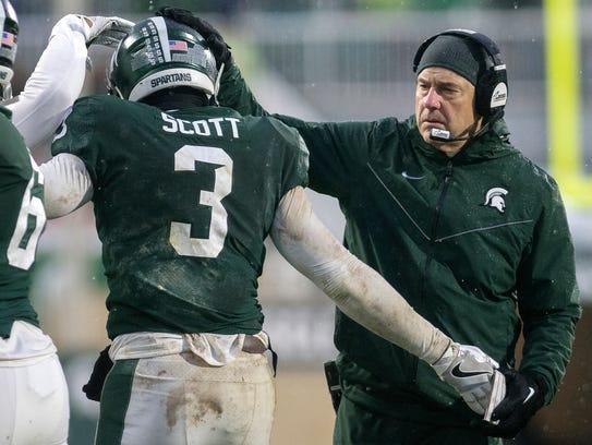 Michigan State head coach Mark Dantonio, right, congratulates