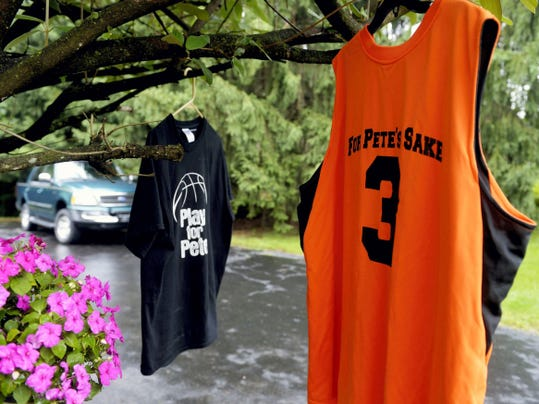 Two commemorative shirts featuring Peter Falci's name and basketball jersey number hang from a tree outside the Falci family's Manchester Township home before his July 4 graduation party.
