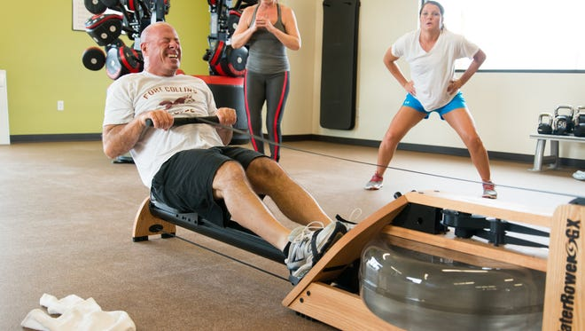 Tom Kane strains against the rowing machine while Kristine (right) and Kathleen Dalton (center) perform squat jumps as part of a Shockwave Functional Training class at Reve Fitness in Jessup Farms.