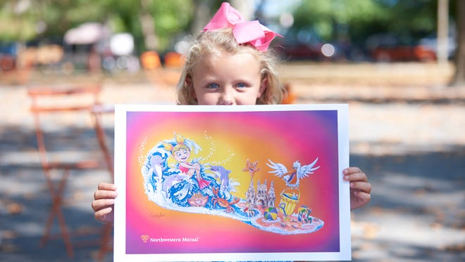 Edie Gilger, 7, of South Carolina, shows a drawing of the float she'll ride in the Rose Parade. The float highlights progress against childhood cancer.