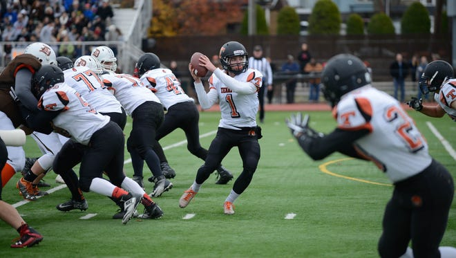 Tenafly quarterback Justin Bershadsky (White No. 1) looking to pass the ball at the annual Thanksgiving game against Dumont on Nov. 24, 2016.