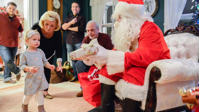 Joan Notar leads Hailey Battista, 2, of Pompton Plains to collect a present from Santa at the Notar home on Dec. 18, 2016. The Notars hosted their 45th annual open home visit with Santa, inviting children and families from their Pompton Plains neighborhood to celebrate the holiday season. The event has seen upwards of 20 children some years and has trickled down through generations to include the children of children that come to see Santa and the Notars.