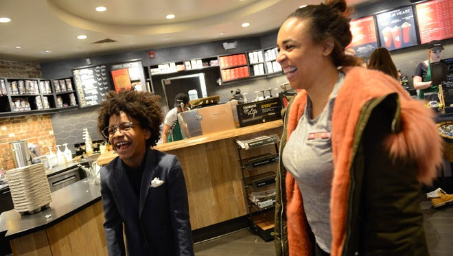 """Lisa Howard and her son, 12-year-old Englewood cookie baker """"Mr. Cory"""" Nieves, at the Englewood Starbucks the day after Christmas. Nieves received a teddy bear as a gift from the store, as he uses the location as a base for many his business operations and has made friends with the staff."""