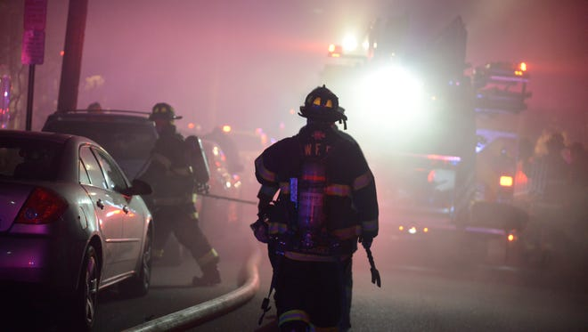 Firefighters make their way down Boiling Springs Avenue during a two-alarm fire on Dec. 31 in East Rutherford.