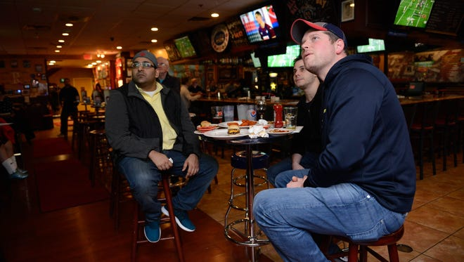 Karan Datwani of New York City, Joe Pedevill of Tenafly and Sean MacIsaac of Rochelle Park watch football at Redd's Restaurant, Bar & Banquets in Carlstadt on Sunday. The crowd was small for the Green Bay Packers and Atlanta Falcons game as both the local Giants and Jets are out of the playoffs.