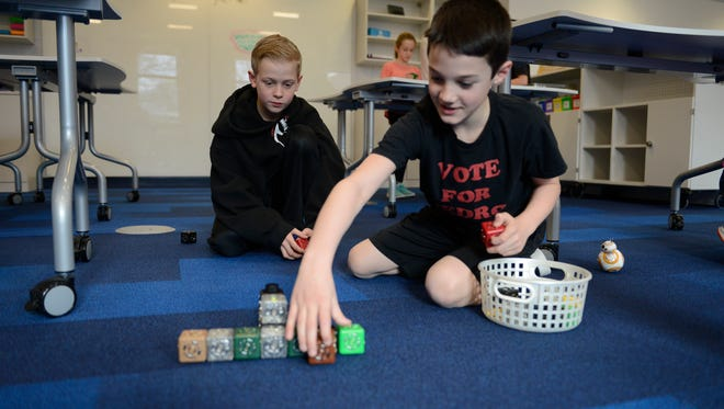Students engage in a makerspace activity with a robot toy during Brookside Elementary School's Learning Commons period last Thursday. Brookside, in Allendale, offers students a chance to come to their new library during their lunch periods to take part in creative and tech activities or just do homework.