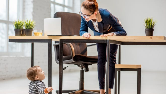Young and elegant businessmam with her baby son playing on the floor at the white office interior