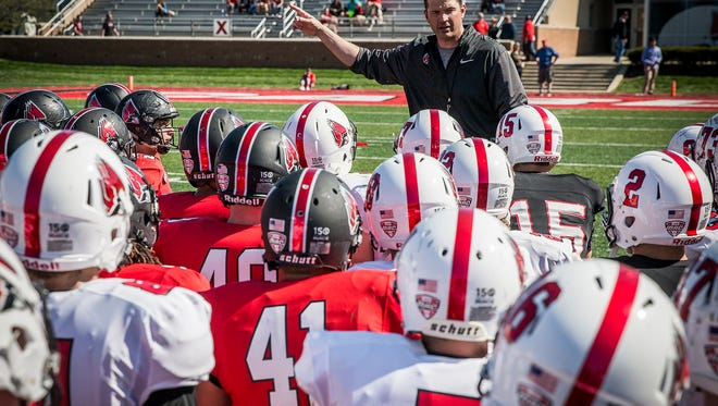 Head coach Mike Neu talks to his players about getting more fan involvement after the team's Spring game at Scheumann Stadium Saturday afternoon.