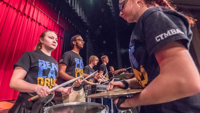 Battle Creek Central students Mackenzie Scupholm (left) and Amia Packer (right) rehearse as part of the drum line Tuesday at W.K. Kellogg Auditorium in Battle Creek.