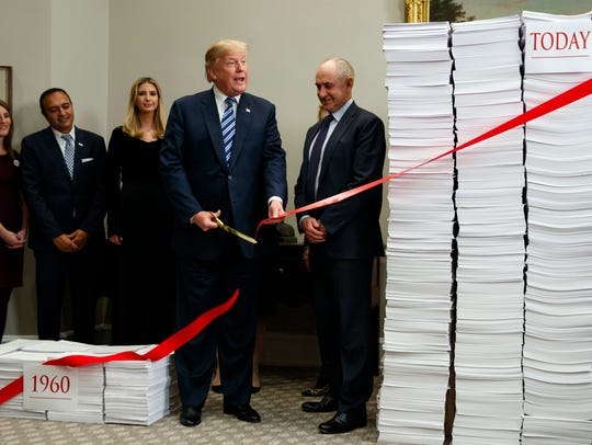 President Donald Trump cuts a ribbon during an event