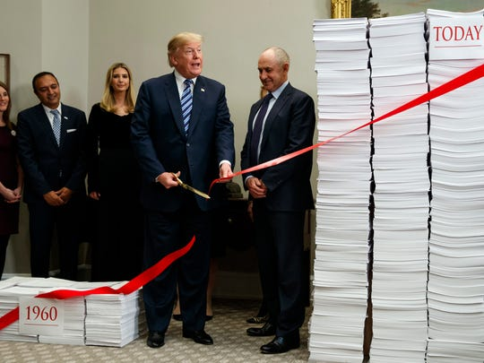 President Donald Trump cuts a ribbon during an event on federal regulations in the Roosevelt Room of the White House, Thursday, Dec. 14, 2017, in Washington.