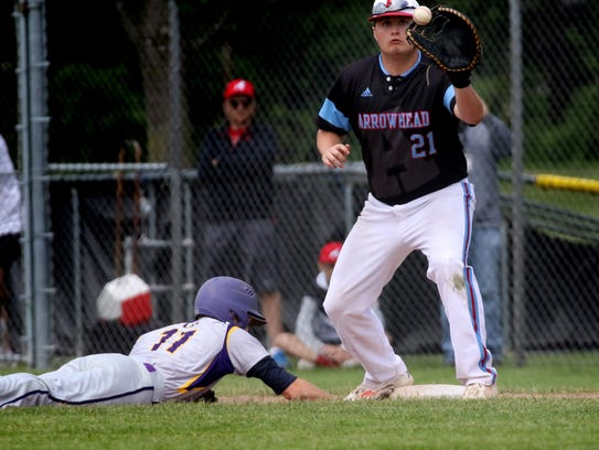 Oconomowoc's Nathan Platter dives back into first ahead of the throw to Arrowhead's TJ Snedden in a sectional semifinal Tuesday.