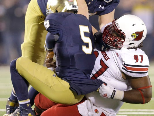 Louisville defensive tackle DeAngelo Brown (97) sacks Notre Dame quarterback Everett Golson (5) during the second half of an NCAA college football game in South Bend, Ind., Saturday, Nov. 22, 2014. Louisville won 31-28. (AP Photo/Nam Y. Huh)