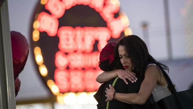 Las Vegas resident Elisabeth Apcar, right, hugs a woman who was working at the concert venue when the massacre happened Sunday night (she wished to remain anonymous), at a makeshift memorial on the Las Vegas Strip, Oct. 4, 2017.