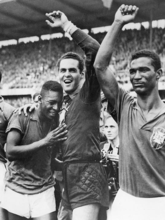 FILE - In this June 29, 1958 file photo Brazil's 17 year-old Pele, left, weeps on the shoulder of goalkeeper Gilmar Dos Santos Neves, after Brazil's 5-2 victory over Sweden in their World Cup final soccer match, in Stockholm, Sweden. Brazil's Didi is at right. On this day: Brazil wins it first World Cup with Pele scoring twice. (AP Photo/File)