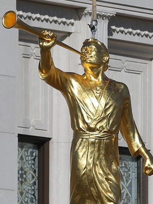 A statue of the Prophet Moroni, whom Mormons believe was a prophet who lived in America during the 4th and 5th centuries and was the angel who presented the golden plates church founder Joseph Smith in 1823, is lifted Oct. 17, 2014, atop the Indianapolis Mormon Temple in Carmel, Ind. The gold-plated statue is 8.5 feet tall, weighs 900 pounds and stands 106 feet above the ground.