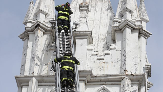 Ossining firefighters inspect a wobbly steeple at First Baptist Church on Church Street, March 13, 2014 in Ossining.