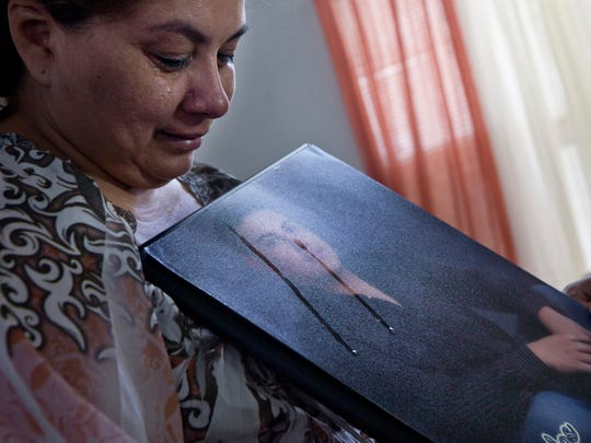 Guadalupe Guerrero holds a photo of her son, Carlos LaMadrid, who was shot near Douglas on March 21, 2011. LaMadrid was smuggling marijuana and was shot as he tried to flee over the border fence into Mexico.