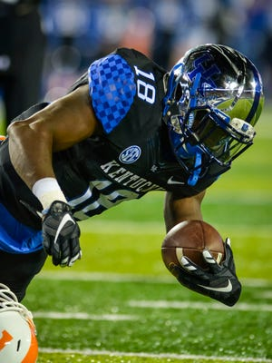 Kentucky's Boom Williams hurts his arm on a run against Tennessee's Justin Martin in the first half Saturday night at Commonwealth Stadium in Lexington.(October 31, 2015)