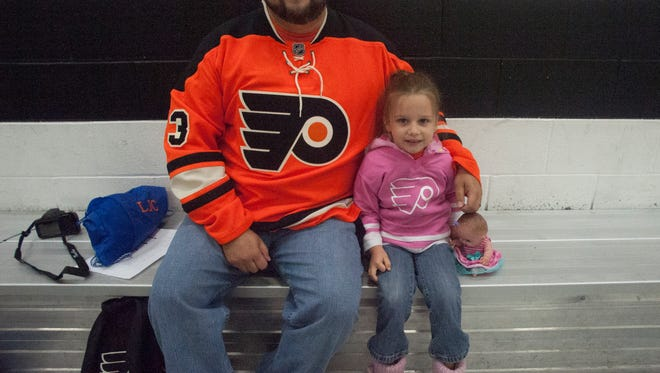 Michael Taylor and daughter Cheyenne, 5, smile as they wait for the Flyers' development camp to start in Voorhees.