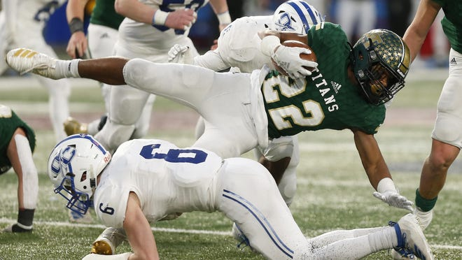 Blessed Trinity's Justice Haynes (22) is sent flying by Oconee County's Liam Lewis (6) during the GHSA high school football AAAA state championship game between Blessed Trinity and Oconee County on Saturday, Dec. 14, 2019, in Atlanta.
