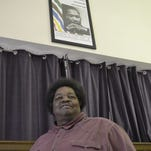 The Rev. L.C. Green stands under a photo of Martin Luther King Jr. in the dining room at Divine Temple Church of God in Christ. Green, who heard King speak in the 1960s, is the founder and pastor of Divine Temple in downtown Green Bay.