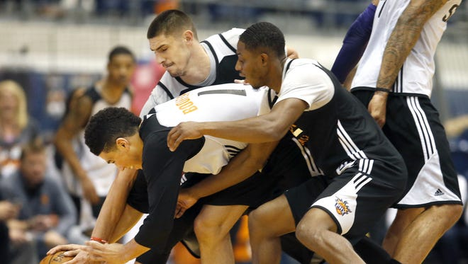 Phoenix Suns players Alex Len, Devin Booker, and Brandon Knight scramble for a loose ball during a preseason scrimmage at Walkup Skydome at Northern Arizona University in Flagstaff on October 2, 2016.