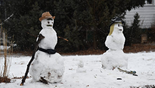 Snowmen stand guard during a brief snow near City Park on Sunday, December 25, 2016.