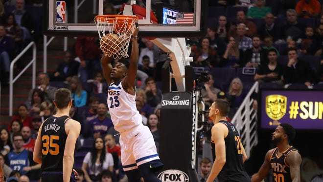 The Timberwolves' Jimmy Butler (23) dunks against the Suns during the first half at Talking Stick Resort Arena on December 23, 2017 in Phoenix, Ariz.