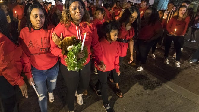 Edithe Delhomme, mother of Aden Williams, is surrounded by family and friends as she leads a walk down Congress Avenue Wednesday, Feb. 5, 2020, to the spot where an SUV hit and killed 14-year-old Aden while he was walking to a bus stop Jan. 29.