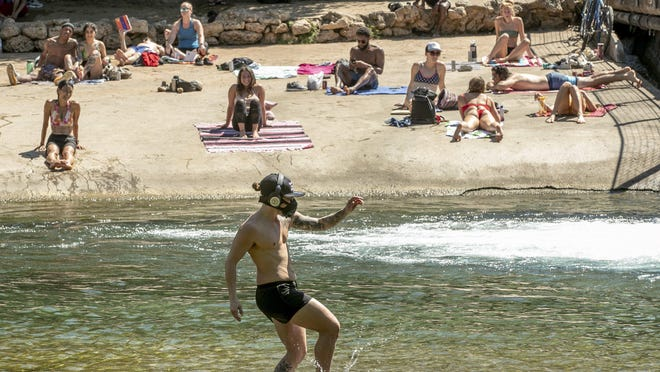 Kristopher McCoy frolics in the cool waters of Barton Creek on Wednesday March 25, 2020.  Dozens of people gathered at Barton Creek below the dam at Barton Springs Pool on the first day of the shelter in place order in Austin due to the coronavirus pandemic.  ??It?s kind of scary what?s going on,? McCoy said.  ?Everybody just needs to start loving one another so we can fix this quickly.?