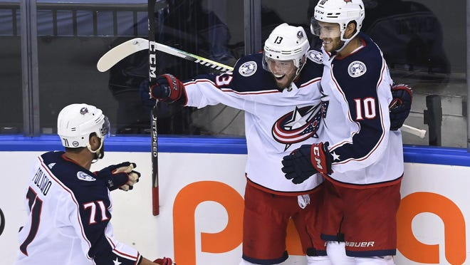 Cam Atkinson, center, is congratulated by Alexander Wennberg, right, and Nick Foligno after breaking the scoreless tie early in the third period Sunday night.